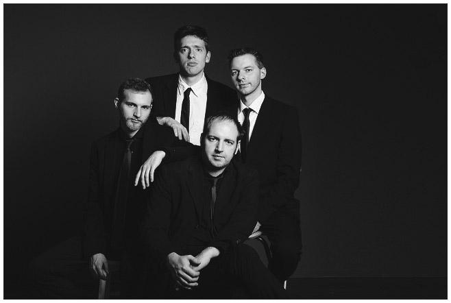 Familienfoto von vier Brüdern im Stil der Beatles aufgenommen vor dunklem Hintergrund im Fotostudio von professionellem Familienfotografen © Fotostudio Berlin LUMENTIS