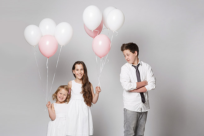 Kinderfotos von drei Geschwistern mit weißen und rosa Luftballons bei Kinderfotoshooting in Berliner Fotostudio © Fotostudio Berlin LUMENTIS
