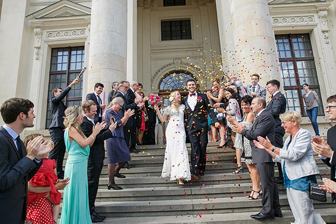 Hochzeitsreportagefoto von Brautpaar im Konfettiregen aus Konfettikanonen nach freier Trauung im Französischen Dom, Berlin © Hochzeitsfotograf Berlin www.hochzeitslicht.de