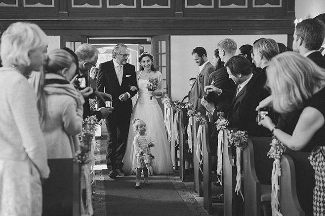 Professionelles Hochzeitsfoto vom Einzug der Braut bei Trauung in Feldsteinkirche Wulkow aufgenommen von Berliner Hochzeitsfotografin © Hochzeitsfotograf Berlin www.hochzeitslicht.de