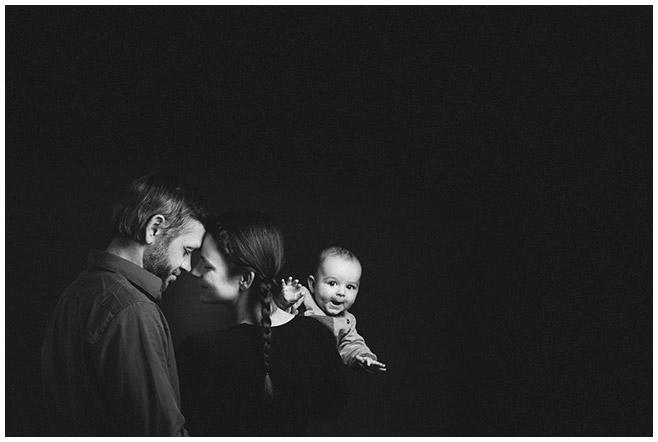 Familienfoto von kleiner Familie vor dunklem Hintergrund aufgenommen bei Familien-Fotoshooting in Berlin © LUMENTIS Fotostudio Berlin