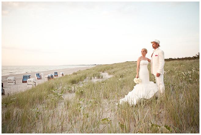Hochzeitsfotografie von Braut und Bräutigam auf Düne mit Strand und Strandkörben im Hintergrund, Ostsee © Hochzeitsfotograf Berlin www.hochzeitslicht.de