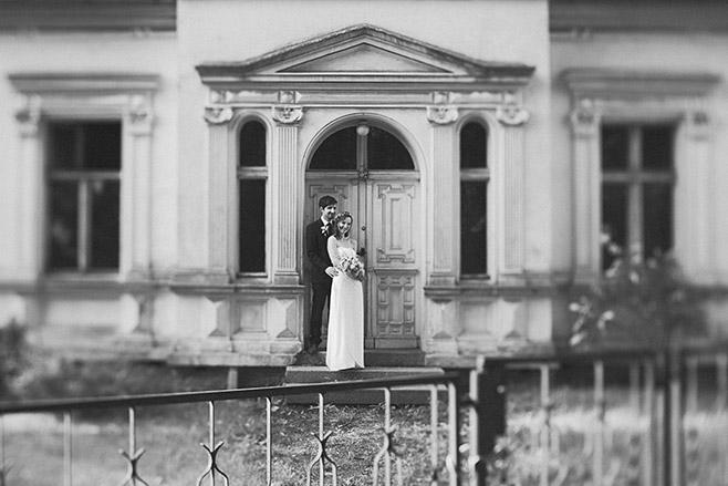 Schwarz-Weiß Hochzeitsfoto von Braut und Bräutigam vor Villa bei Spreewald-Hochzeit aufgenommen von professioneller Hochzeitsfotografin © Hochzeitsfotograf Berlin www.hochzeitslicht.de