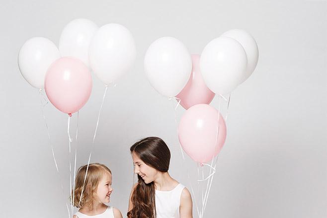 Kinderfoto von zwei Schwestern mit weißen und rosa Luftballons aufgenommen bei Kinderfotoshooting mit professionellem Kinderfotograf Berlin © Fotostudio Berlin LUMENTIS