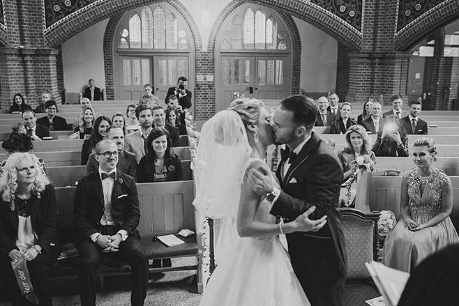 Hochzeitsreportagefoto von Hochzeitskuss bei kirchlicher Trauung in Heilige-Geist-Kirche aufgenommen von professionellem Berliner Hochzeitsfotografen © Hochzeitsfotograf Berlin www.hochzeitslicht.de