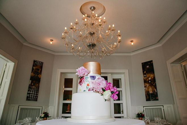 Dreistöckige Hochzeitstorte mit Dekor in Kupfer und buntem Blumendekor bei Hochzeit in Villa Blumenfisch © Hochzeitsfotograf Berlin www.hochzeitslicht.de