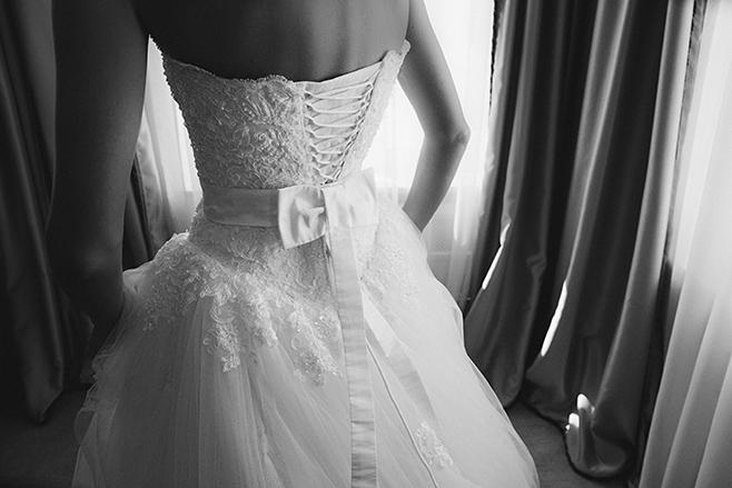 Hochzeitsbilder von Vorbereitungen der Braut Detailaufnahme von Brautkleid mit Spitze und Schnürung am Rücken aufgenommen von professioneller Hochzeitsfotografin © Hochzeitsfotograf Berlin www.hochzeitslicht.de